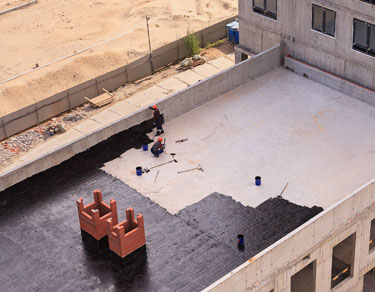 Two Workers Conduct Waterproofing Of The Roof With Bitumen. View